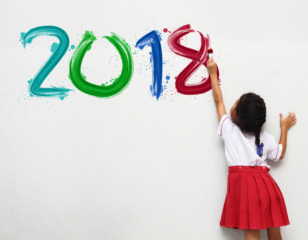 little girl holding a paint brush painting happy new year 2018 on a white wall background