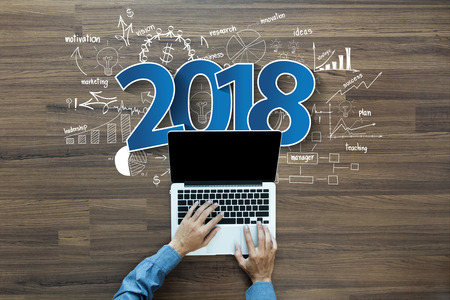 2018 new year business success, Creative thinking drawing charts and graphs strategy plan ideas wooden table background, Inspiration concept with businessman working on laptop computer PC, Top View Banco de Imagens - 85264293
