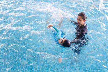 レジャー センターでコーチと一緒に泳ぐことを学ぶ少女