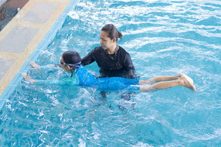 Girl learning to swim with coach at the leisure center