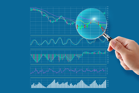 Stock Analysis ideas concept hand holding Magnifying glass trading graph of stock market on the virtual screen