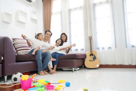 Happy asian family in living room at home, togetherness relaxation concept 스톡 콘텐츠