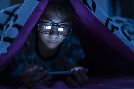 Girl wear glasses using mobile phone on dark bed in the bedroom Stock Photo