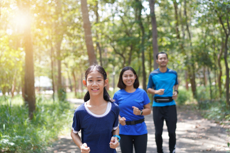 Asian family exercising and jogging together at the park Stockfoto
