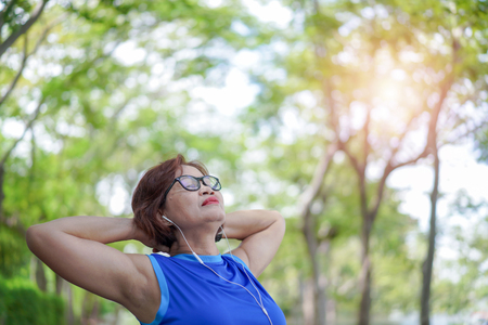 Senior asian woman relaxed listening to music in the park, Exercise sport activity concept Фото со стока