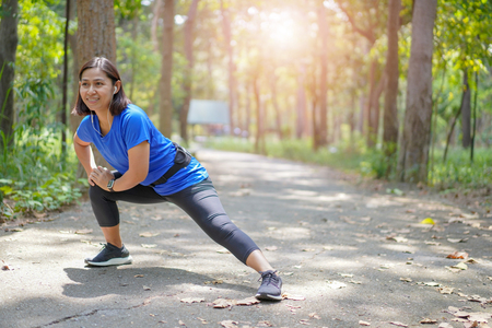 Asian woman stretch muscles at park and listening to music. Athletic exercising together outdoor. Fit runners stretching before running outdoors