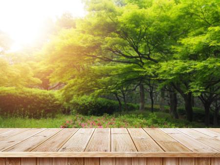 Tischplatte und Unschärfenatur des Hintergrunds, des grünen Grases und des Baumschönheitsnaturhintergrundes. Standard-Bild