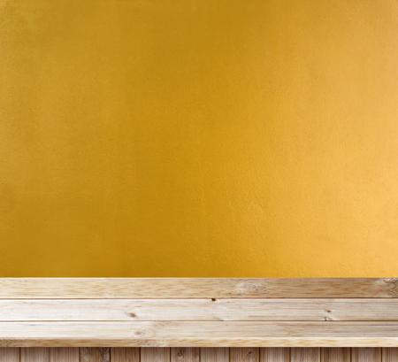 Tischplatte aus Holz auf gelber Wandstruktur Standard-Bild
