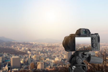 Digital camera over tripod on cityscape with blue sky at sunset