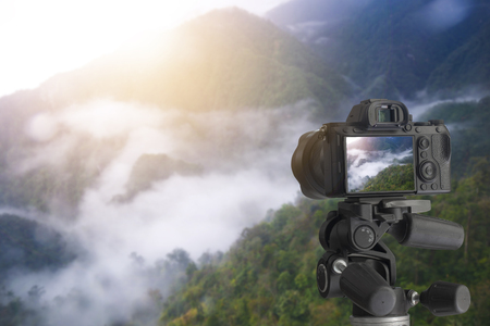 Digital camera backside over tripod on high mountains with fog
