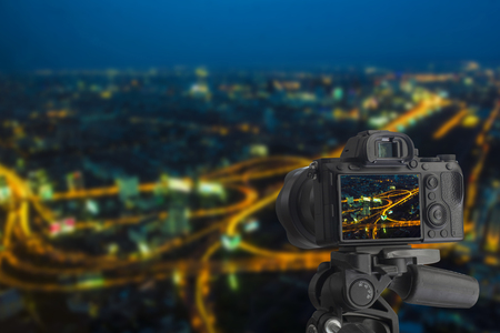 Digital camera over tripod on cityscape buildings at night, Cityscape Bangkok downtown long exprosure at night