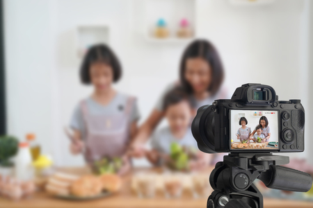 Mother and daughter cooking in the kitchen at home, With recording making video blogger camera for their blog