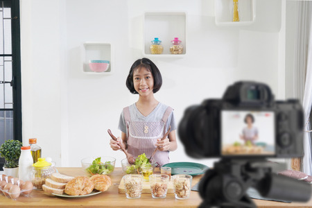 Little girl cooks in the kitchen at home, With recording making video blogger camera for their blog
