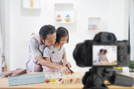Father and daughter cooks in the kitchen at home, With recording making video blogger camera for their blog
