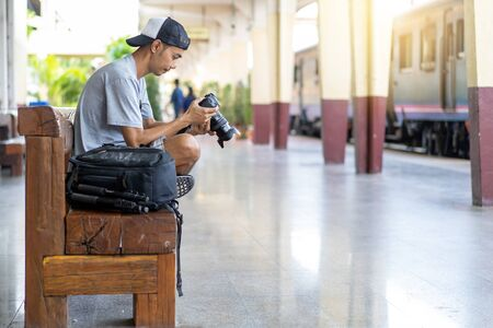 Asian man Traveler with check the image file from the camera and backpack, at train station in Thailand