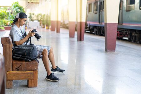Asian man Traveler with holding photo camera and backpack at train station in Thailand Imagens