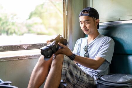 Asian man Traveler with hand holding photo camera and backpack, Sit on the old train seat at Thailand