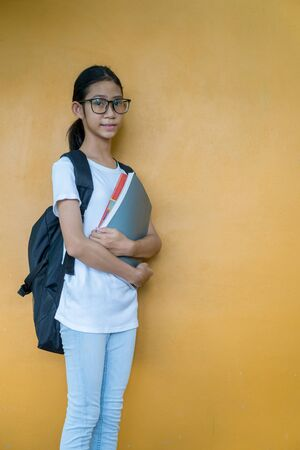 Asian little schoolgirl with backpack holding book or notebook on yellow background Imagens