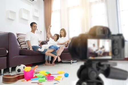 Happy asian family in living room at home, togetherness relaxation concept Imagens
