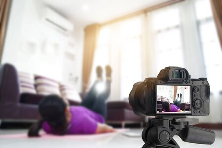 Asian women exercise workout at home, With recording making video blogger content