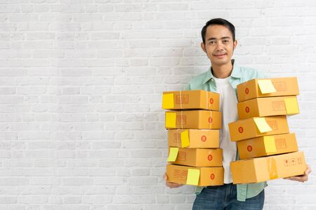 Asian man holding carry brown parcel or cardboard boxes on brick wall background, selling online start up small business owner e-commerce ideas concept