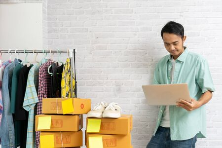 Asian man stand working laptop computer on brick wall, selling online start up small business owner e-commerce ideas concept
