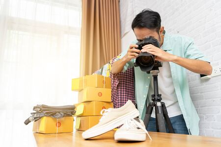 Asian man taking photo to shoes with digital camera for post to selling online on the internet, Start up small business owner e-commerce ideas concept