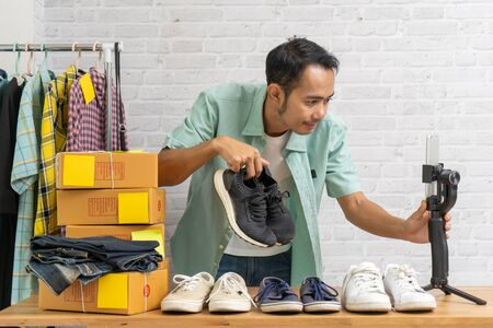 Asian man using smart mobile phone taking live selling shoes online, Recording making video blogger camera Start up small business owner e-commerce ideas concept