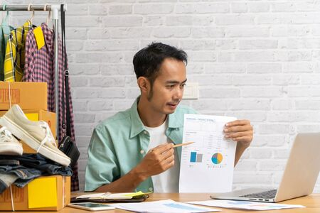 Asian man hand pointing at business document during discussion at meeting on laptop computer, Selling online start up small business owner, e-commerce ideas concept Imagens