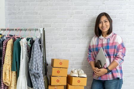 Asian women holding laptop computer selling online start up small business owner, e-commerce ideas concept