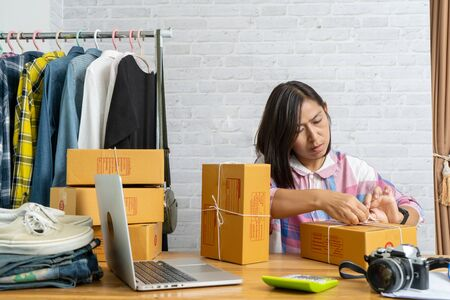Asian women start up small business owner packing cardboard box, e-commerce ideas concept