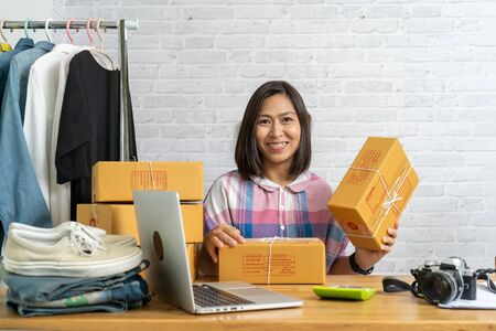 Asian women start up small business owner holding packing cardboard box, e-commerce ideas concept Imagens