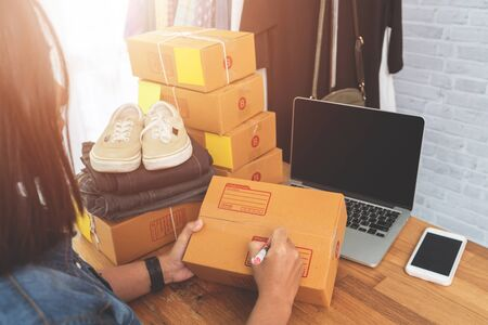 Online selling e-commerce shipping idea concept, Women freelance start up small business owner packing cardboard box at workplace