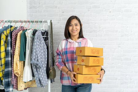Asian woman carry brown parcel or cardboard boxes on brick wall background