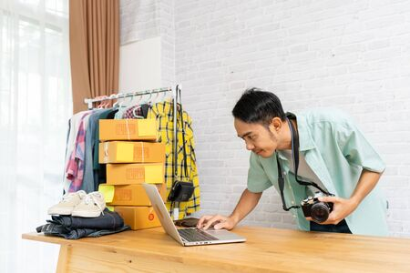 Asian man working laptop computer selling online start up small business owner, With hold the camera ready to take the product e-commerce ideas concept