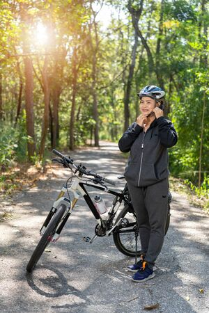 Attractive senior asian woman with bicycle in park Фото со стока