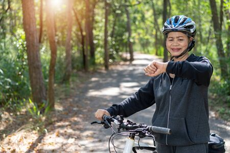 Senior asian woman bicycle in the park, With checking time or heart rate from smart watch