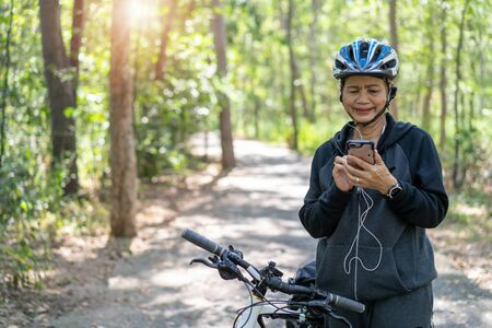 Senior asian woman bicycle in the park, With using smart phone and listening to music