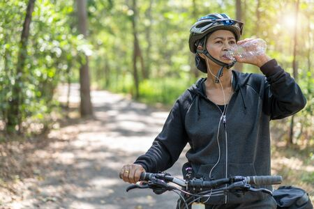 Attractive senior asian woman drinking water from bottle with bicycle in park