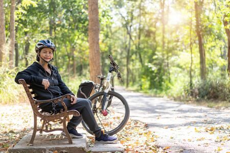 Senior asian woman bicycle with sitting in the park, With using smart phone and listening to music