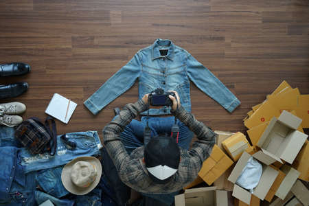 Top view of men using digital camera shooting take a photo jeans jacket, With fashion accessories on wooden floor with postal parcel, Selling online ideas concept