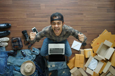 Top view asian man successful working laptop computer, With fashion accessories and postal parcel on wooden floor from home. Selling online ideas concept