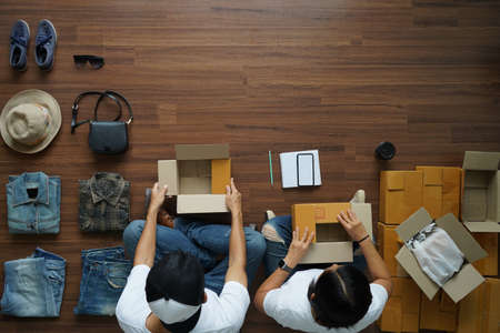 Top view women and men selling online start up small business owner, With fashion clothes accessories and postal parcel in her home