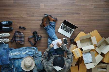 Top view man writing in note book is freelancer with her private business at home office, Selling online start up small business owner SME idea concept