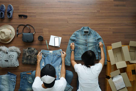 Women and men selling online start up small business owner, Top view on wooden floor with fashion clothes accessories and postal parcel work at home