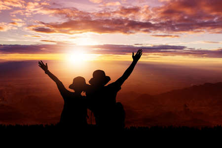Silhouette of couple on the top hills and sky sunset background Zdjęcie Seryjne