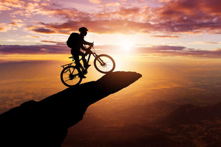 Silhouette of a Cyclist on the top hills and sky sunset background