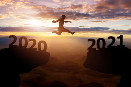 Success 2021 new year concept.Silhouette man jump between 2020 with hills and sky sunset background Zdjęcie Seryjne - 160695251
