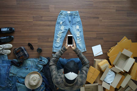 Top view of men using smart phone shooting take a photo jeans, Selling online start up small business owner  ideas concept Zdjęcie Seryjne