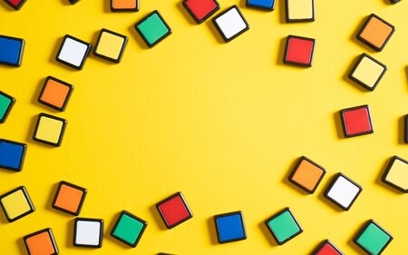Top view of yellow background and colorful squares from cubes. Educational background for school, smartness, toy and puzzle